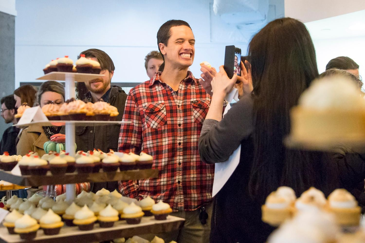 A guest of the VIP Wedding Tasting tries one of the mini cupcakes at Trophy Cupcakes at the Bravern. Guests were able to try the delectable cupcakes, 6-inch cakes, macarons, meringues, and other goodies on display while sipping champagne. (Sy Bean / Seattle Refined)<p></p>