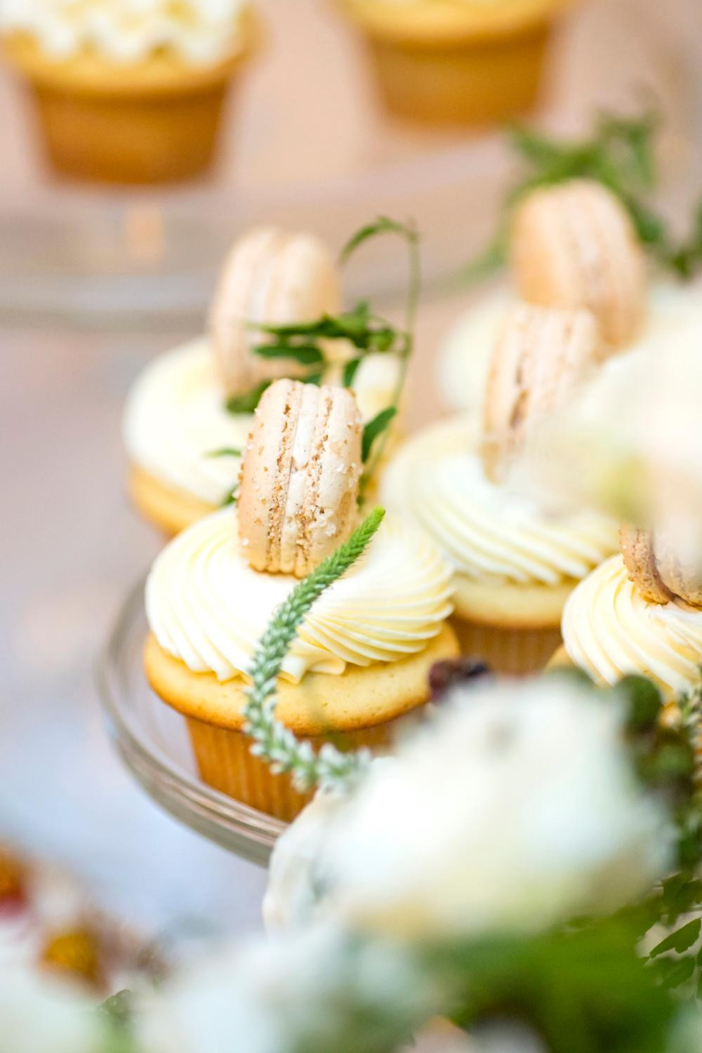 Vanilla Vanilla Cupcakes topped with Cinnamon Toast Macarons are on display for guests of the VIP Wedding Tasting at Trophy Cupcakes at the Bravern. Guests of the tasting were able to try the delectable cupcakes, 6-inch cakes, macarons, meringues, and other goodies on display while sipping champagne. (Sy Bean / Seattle Refined)<p></p>